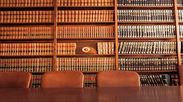 Image of boardroom with shelves of law books in background. Three chairs at wooden boardroom table directly in front of shelves.