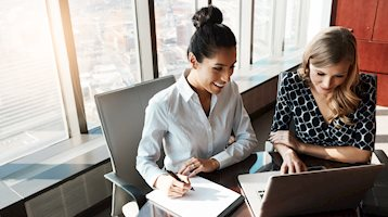 Two women sitting at office desk in front of laptop. One women navigates laptop, as other woman takes notes on paper notepad.